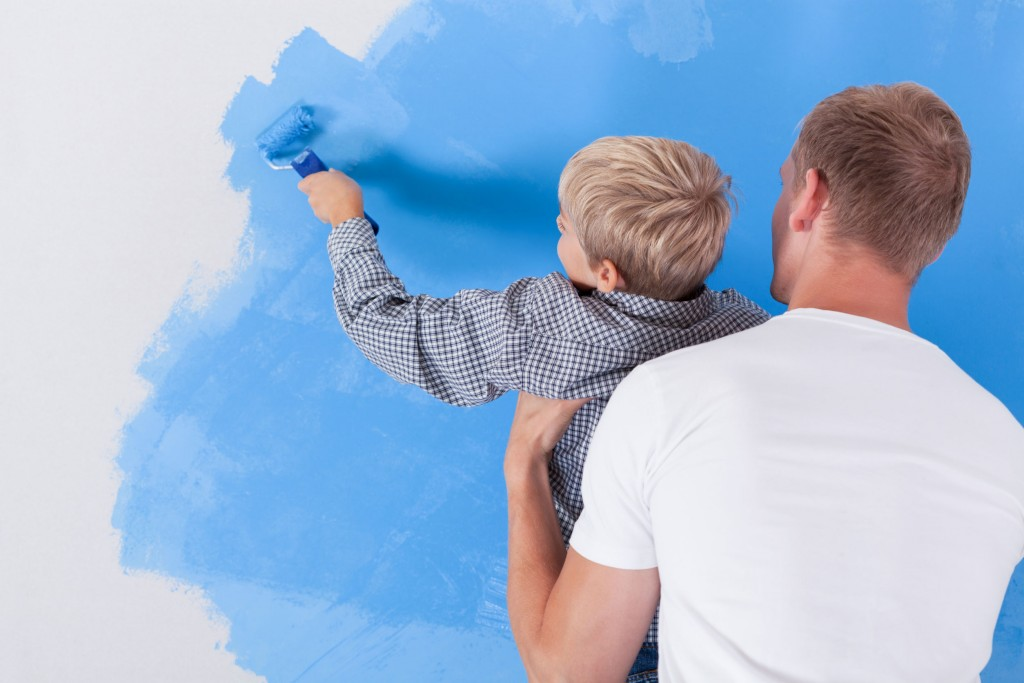 34889865 - horizontal view of boy painting wall in dad's arms