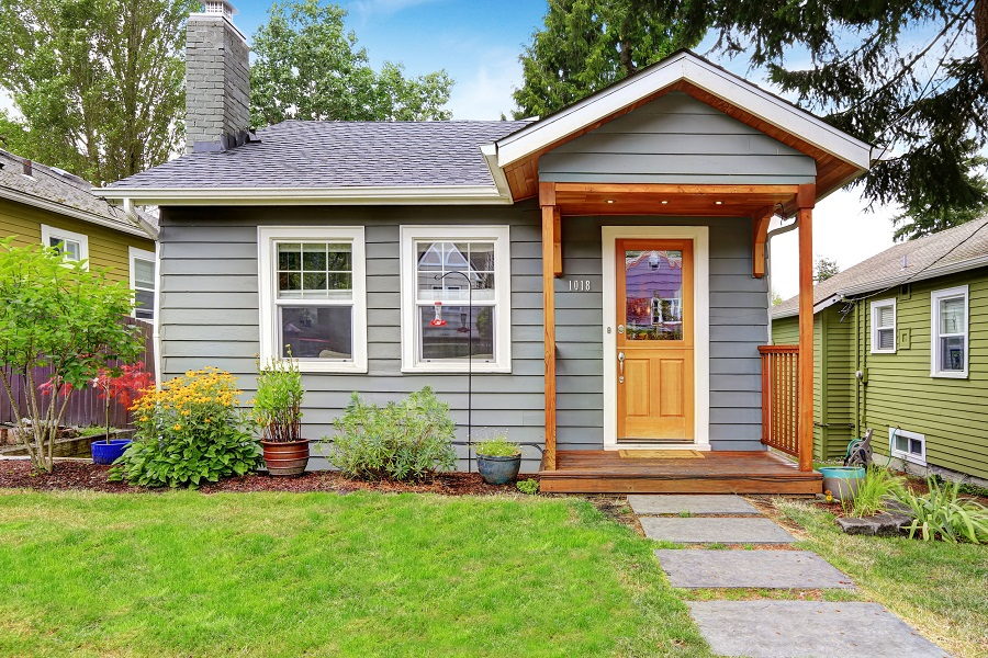 31574495 - small grey house with wooden deck. front yard with flower bed and lawn