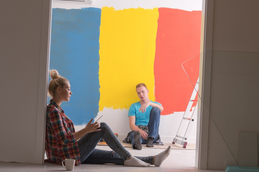 73487057 - happy young couple relaxing after painting a room in their new house on the floor